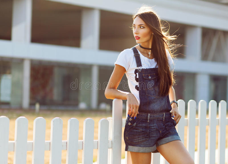 Street fashion photo of young beautiful woman in casual jeans sh. Orts and white shirt over white wooden fence stock photo