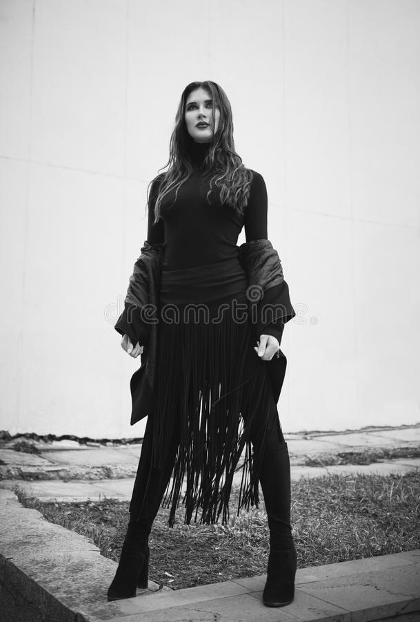 Street fashion: portrait of cute young girl in black. Black and white stock photo