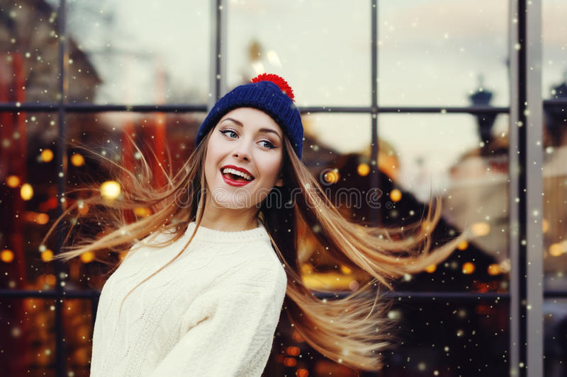 Street fashion portrait of smiling beautiful young woman playing with her long hair. Lady wearing classic winter knitted royalty free stock image