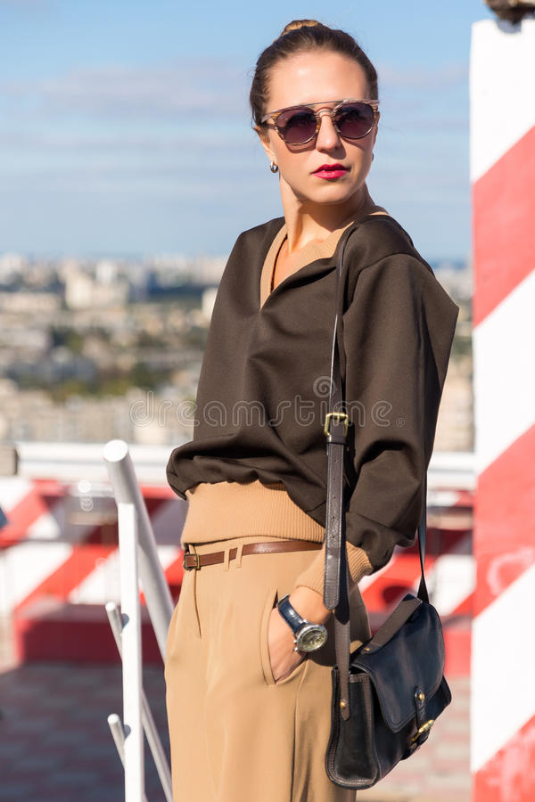 Street fashion portrait stylish pretty woman with sunglasses and bag posing in city on evening sunny sunset royalty free stock photos