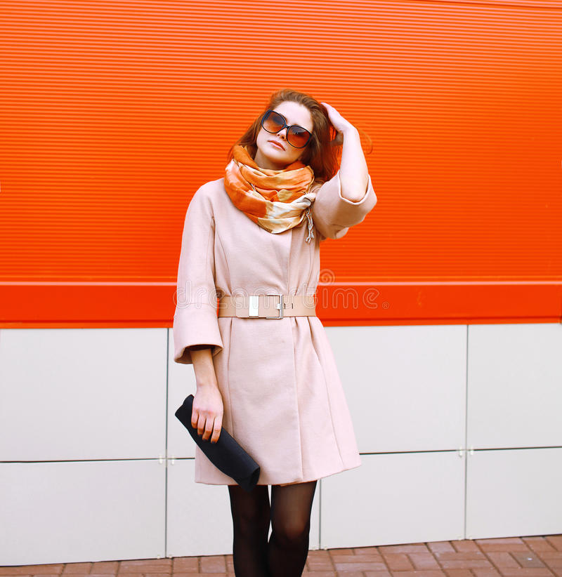 Street fashion pretty stylish sensual woman in coat and sunglasses with bag clutch posing outdoors against colorful wall in the c stock photos