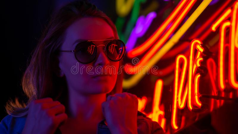 Street fashion young girl with sunglasses, neon light red blue, nightlife and trendy lifestyle stock photos