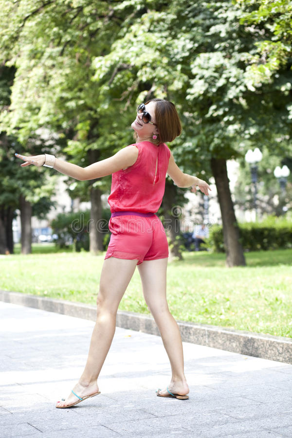 Street fashion. Young woman in red shorts and a blouse stock photos