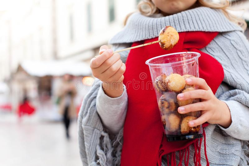 Street fast food fritters on Christmas market. Kid with local festive Croatian sweets, dessert. royalty free stock photography