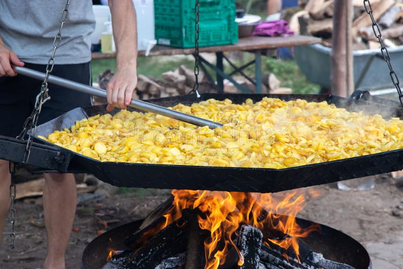 Street festival of potatoes in Germany. Traditional fried potatoes with onions over an open fire in a huge frying pan. A man is royalty free stock photography