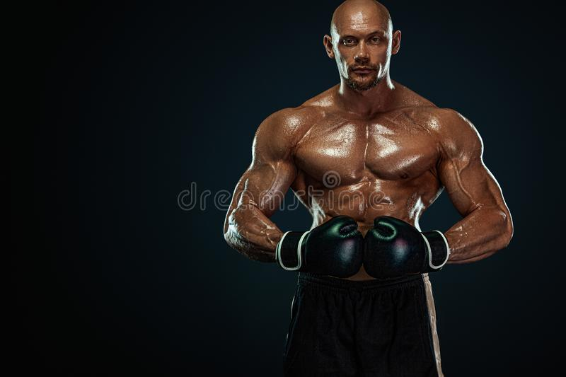 Sportsman, man boxer fighting in gloves on black background. Fitness and boxing concept. stock photography