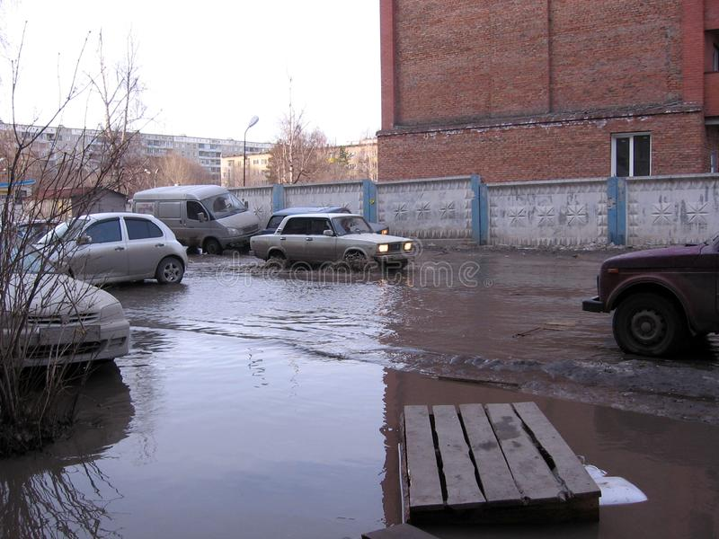 Russia, Novosibirsk, April 15, 2013: a street flooded with dirty water in the city in the spring lies a makeshift bridge over stock photos