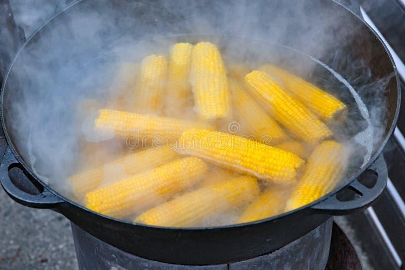 Street food boiled corn outdoors in metal pot closeup. Street food boiled organic corn outdoors in big metal pot closeup stock photography