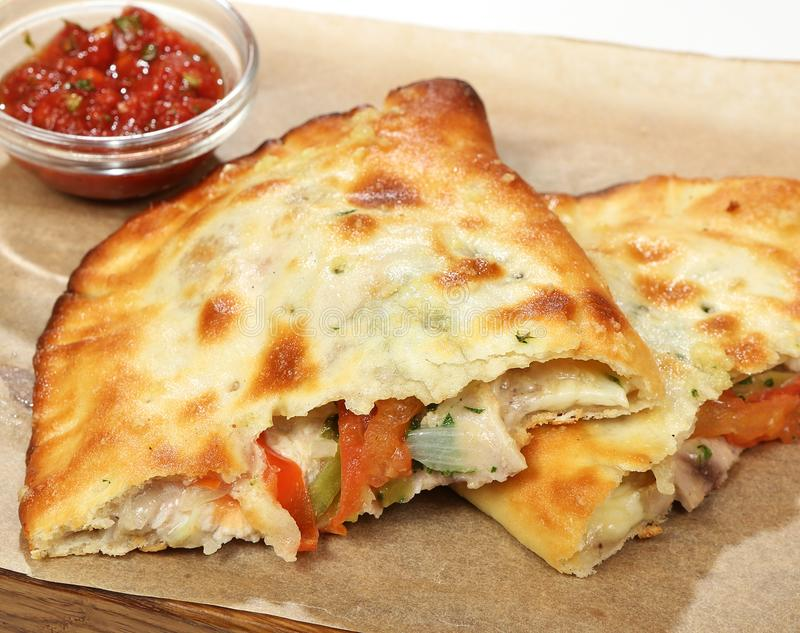 Street food chicken quesadilla cheese, tomatoes, gherkins, onions, Caesar sauce royalty free stock photography