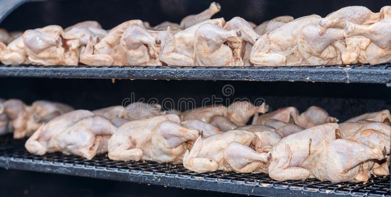 Street food. chickens with spices are ready for Smoking or baking. In a large metal oven on coals. Selective focus royalty free stock photos