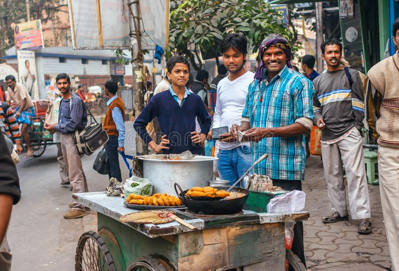 Street food cooker having fun with customers and sell local fast-food on crowded city area royalty free stock photography