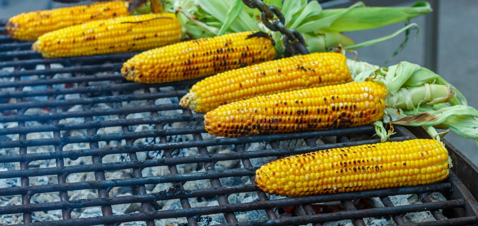 Street food. Corn on the cob, grilled on coals. Selective focus royalty free stock photography