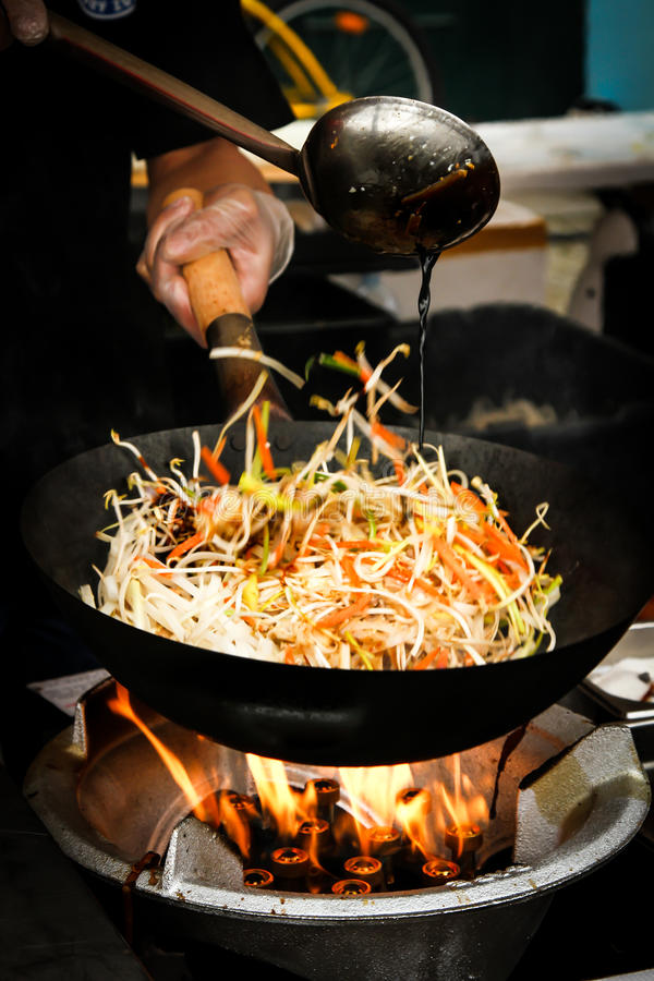 street food. fried noodles in a wok with chicken royalty free stock photography