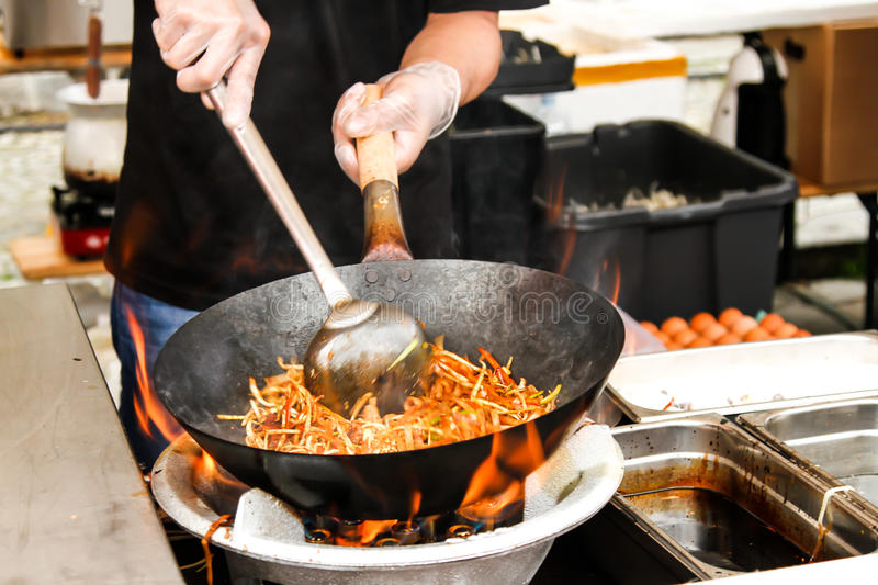 street food. fried noodles in a wok with chicken stock photo