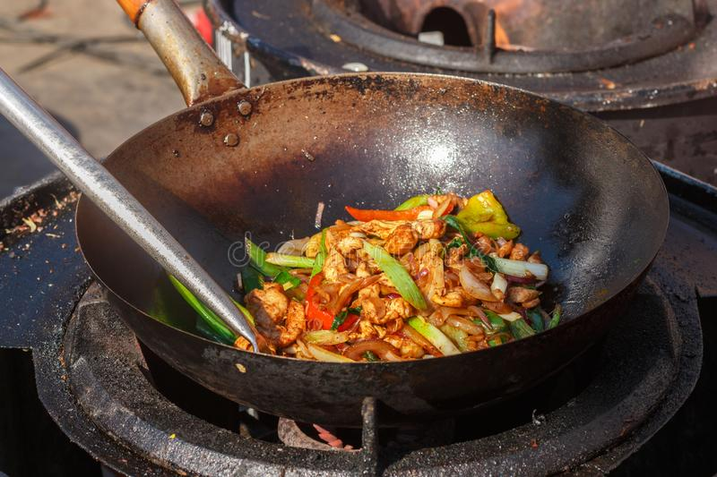 Street food. Fry the meat in a wok with vegetables - onions, bell peppers, tomatoes, seasonings and spices. Stir fry. Stirfry. royalty free stock photos