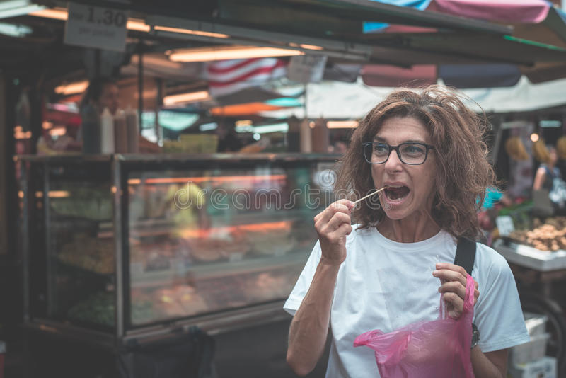 Street food in Kuala Lumpur, Malaysia. Traveling woman eating voraciously chopped fruit from local market vendor. Toned image, ins stock photography