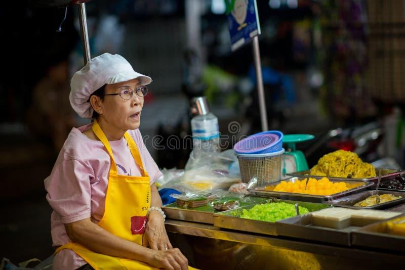 Street food at the Night Market in Hua Hin. Hua Hin, Thailand – January 17, 2013: Thai woman sells street food stall at the night market in Hua Hin. The stock image