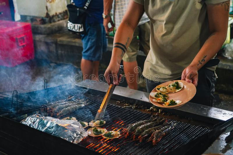 Street food at night in Phu Quoc island in Vietna. A man chef cooking at Grilled seafood ember stove royalty free stock photography