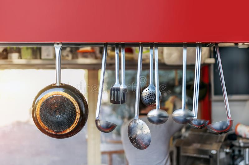 Street food open shop-window with stainless steel set of kitchenware utensils. Blurred chief cook preparing meal on background. Signboard, copyspace stock photos
