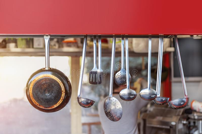 Street food open shop-window with stainless steel set of kitchenware utensils. Blurred chief cook preparing meal on background. Signboard, copyspace royalty free stock photo