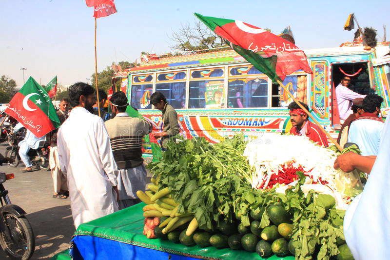 Street Food outside PTI Rally in Karachi, Pakistan. A Street Hawker sells some cold spiced fruits and vegetables as Hundreds of Thousands of People gather in stock photo