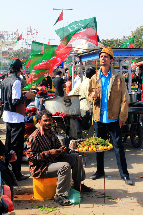 Street Food outside PTI Rally in Karachi, Pakistan. A Street Hawker sells some cold spiced fruits and vegetables as Hundreds of Thousands of People gather in royalty free stock photography