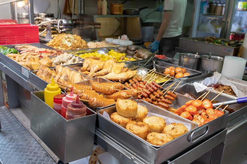 A street food stall in Hong Kong selling different types of deep fries and barbecued food. Demonstrating Asian street food culture. For illustrating travelling stock photos