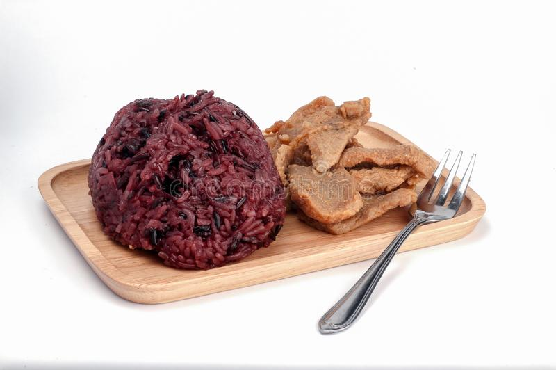 Street food thailand, black sticky rice with fried pork on wooden plate royalty free stock image