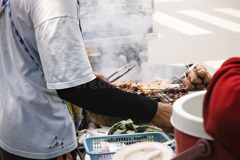 Street food vendor. A food vendor selling grilled chicken on the street of bangkok, thailand stock photography