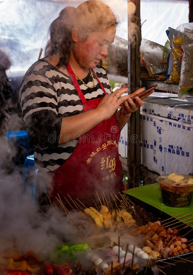 Street food vendor accepts orders on smartphone stock photo