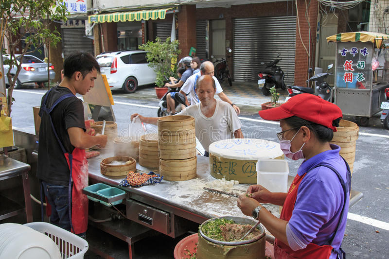 Street food vendor in Kaohsiung, Taiwan, preparing the steamed Xiao Long Bao, a traditional chinese dish invented in Shanghai. Kaohsiung, Taiwan - August 9,2015 royalty free stock images