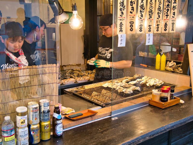 A street food vendor prepares oysters for cooking with freshly cooked oysters for sale at a stall on Miyajima Island, Japan stock image