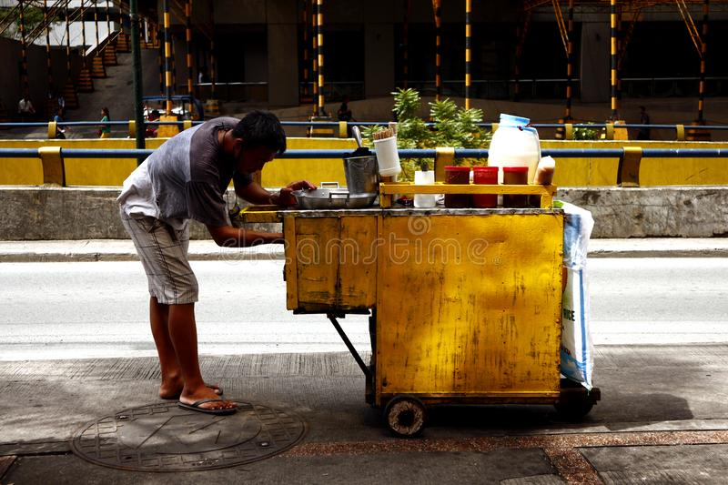 A street food vendor prepares to cook fish balls and other snack items at his food cart royalty free stock photography