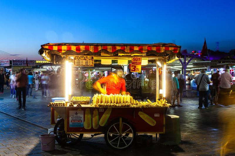 Street food vendor sells corn cobs and roasted chestnuts on the. ISTANBUL, TURKEY - AUGUST 14: Street food vendor sells corn cobs and roasted chestnuts on the royalty free stock images