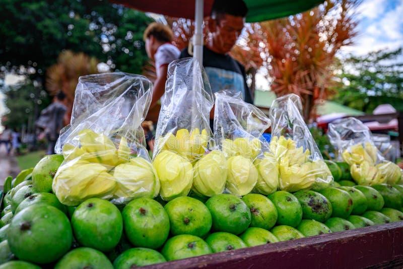 A street food vendor slices fresh green mango which sells on foo. Manila, Philippines - Feb 4, 2018 : A street food vendor slices fresh green mango which sells royalty free stock photo