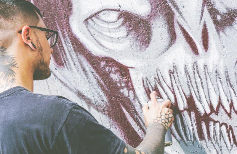 Street graffiti artist painting with a color spray a dark monster skull graffiti on the wall - Urban, lifestyle street art concept stock photos