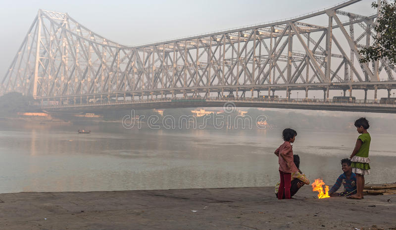 Street kids keep warm on a cold foggy winter morning at Mallick ghat near Howrah bridge at the bank of river Hooghly. royalty free stock photo