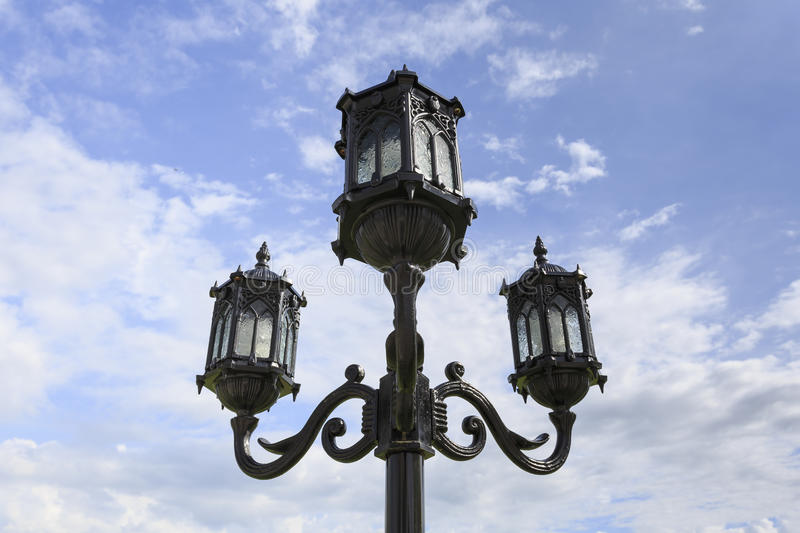 Street lamp against clouds and blue sky. stock image