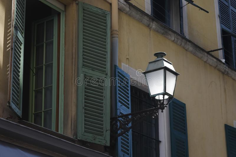 Street lamp on the facade of a building. A street lamp was installed on the facade of a building in the old town of Nice, which is an important city of the royalty free stock images