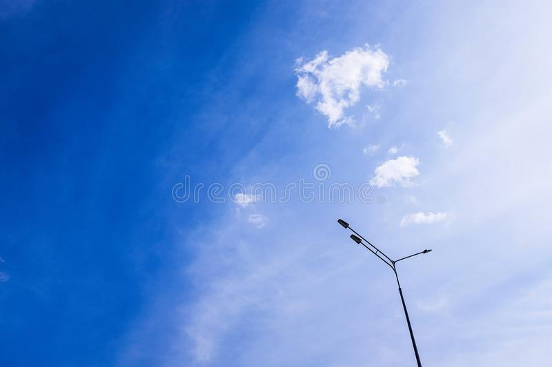 Street lamp, lamppost on a free bright blue sky with white clouds on a summer Sunny day. Idyllic soothing empty background, copy stock image