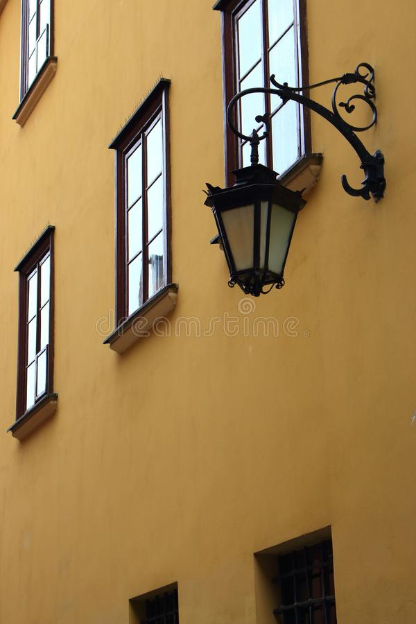 Street lamp lantern with forged metal elements on ancient building with narrow windows. Old facade house. Old town european street. Antique architecture stock image