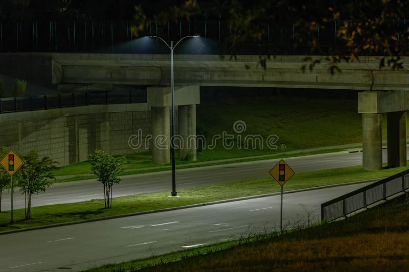 Street lamp next to an underpass. 2 streets going under an underpass with a street lamp lighting the scene, and two traffic light signs posted on either side of stock photo