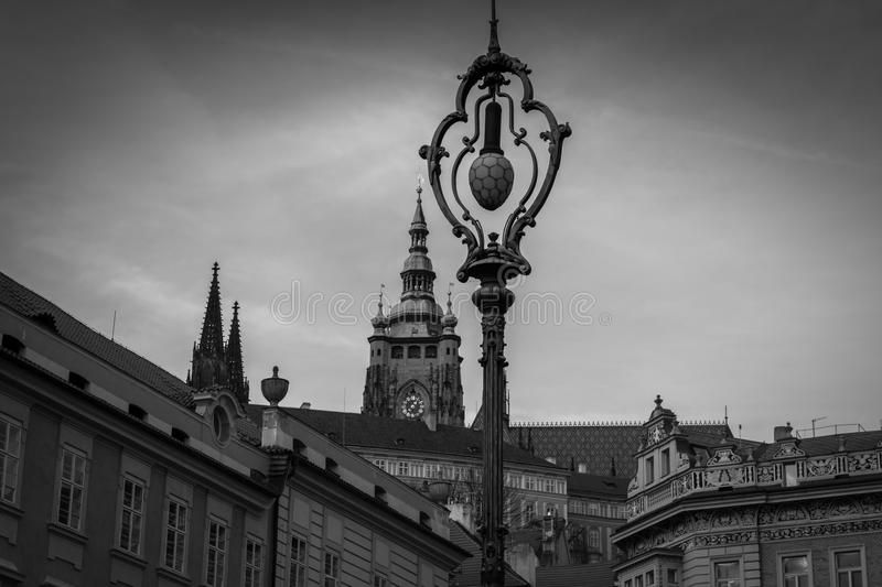 Street lamp in Prague with a watch tower in the background in black and white. Street lamp in Prague Czech Republic royalty free stock photos