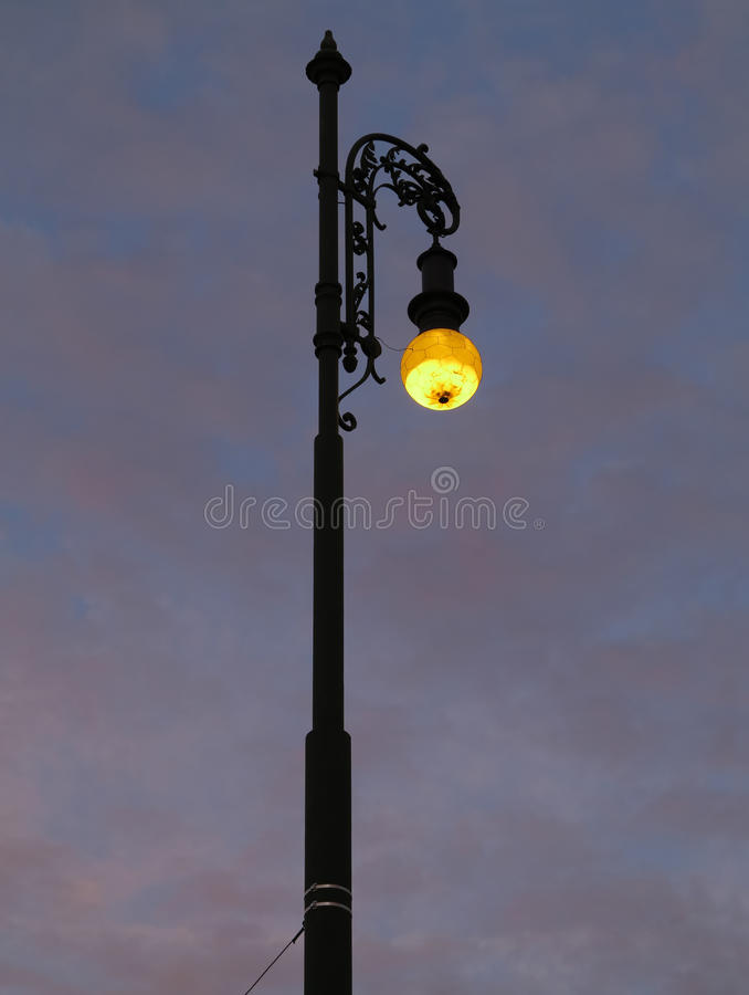 Street lamp shining at dusk royalty free stock photography