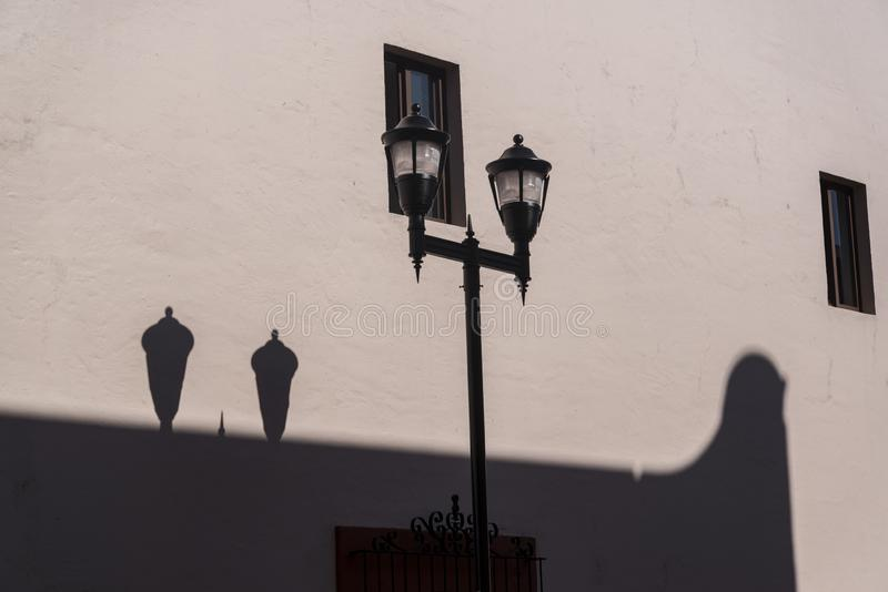Street lamp. Oaxaca, Mexico. Street lamp and stark shadows on the plain wall of a house. Oaxaca, Mexico stock photo