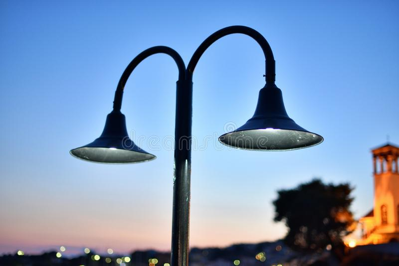 Street lamp with white light shining mysteriously in the sunset of a town stock photo