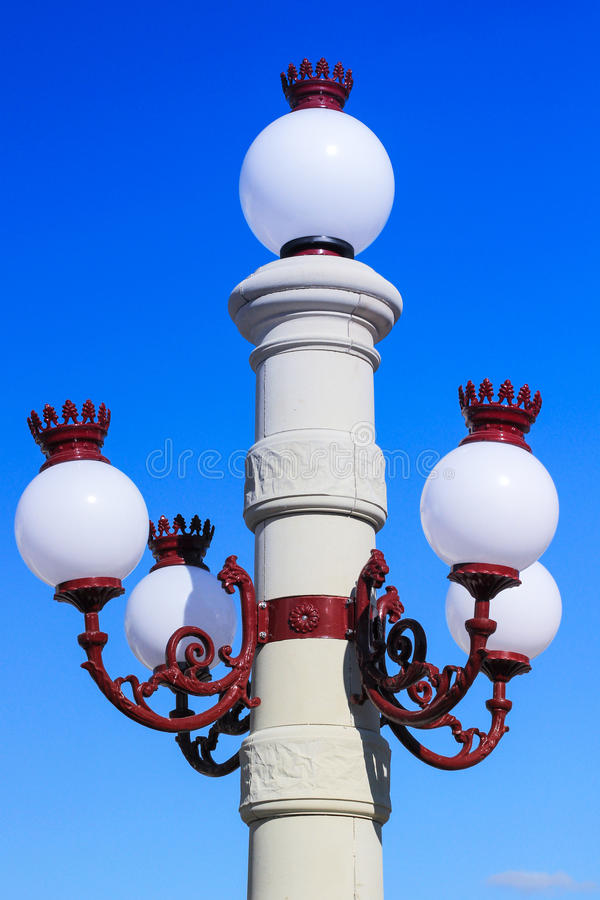 Street lamp with white shades on the background of blue sky. Close up stock image