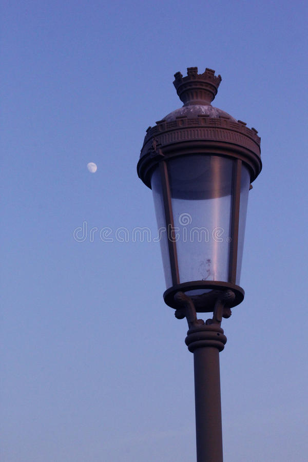 Street lamp with blue sky and a moon background. Street lamp in working mode in the winter night. A blue sky and moon background looks good. Beautiful shot stock photo