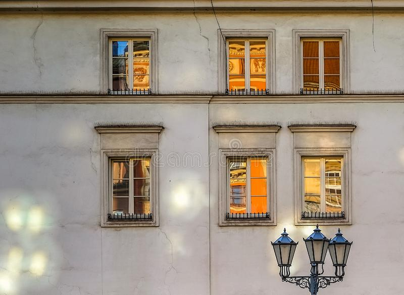 Street lantern and old windows on the wall in Krakow in the evening stock photo
