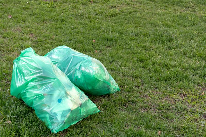 On the street on the lawn two large green plastic bag with garbage. Conceptual photography royalty free stock images